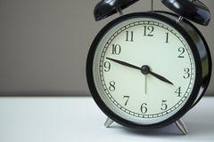 Close up Clock. Classic style alarm clock on white table Royalty Free Stock Photography