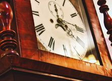 Close up of clock face on an antique grandfather clock with roman numerals stock photography
