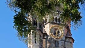 Clock of Kaiser Wilhelm Memorial church behind a tree in Berlin, Germany