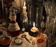 Close up with clock, key, candle, bottles and magic objects. Close up with vintage clock, key, candles, bottles and magic objects. Old pharmacy,  medieval Royalty Free Stock Images