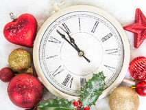 Close up of a clock on new year`s eve with christmas decoration stock photo