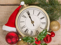 Close up of a clock on new year`s eve with christmas decoration royalty free stock image