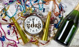 Close up of clock showing Midnight for Celebration of New Year 2. Clock showing Midnight for New Year 2018 surrounded by party objects and Champagne stock image
