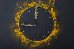 Composition of a clock from spices and green grass on a black background. Royalty Free Stock Image