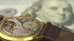 Close up of clockwork drive in a classy watch on the dollar banknote.  stock footage