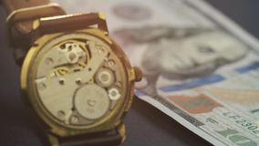 Close up of clockwork drive in a classy watch wich lies on one hundred dollar banknote.  stock footage