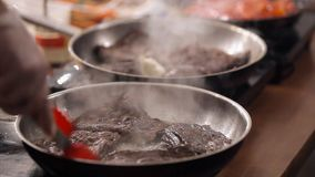 Close up. Close up on cook`s hands . Male hands. The man rummages around meat on a frying pan. Pieces of beautiful meat