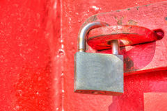 Close up of a closed padlock in a red gate in hdr Stock Photos