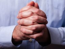 Close up or closeup of hands of faithful mature man praying. Hands folded, interlaced fingers in worship to stock photography