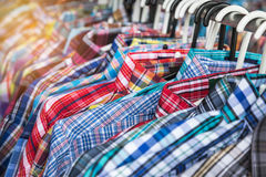 Close up cloth hangers with men shirts on rail. In clothing store Stock Photos