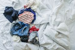 Close up clothes and accessories thrown on unmade bed Royalty Free Stock Images