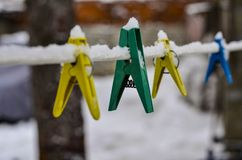Close-up of clothespins for washing clothes, attached to a snow-covered rope against the blue sky and bright sun royalty free stock images