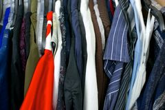 Close up of clothing, red shirt on left. In a closet Stock Photos