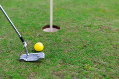 Close up of club and ball near hole on golf field Stock Photo