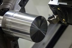 Close up of the CNC lathe. Jaw clamping raw material steel rod .Steel Cylinder part after turning process. Hi-precision CNC machining concept.Raw material steel royalty free stock images