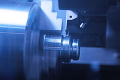 Close-up of a CNC machine at work. Thread cutting on the lathe, CNC high-speed machining Stock Photo
