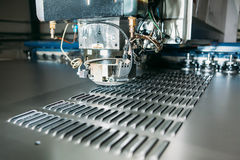 Close up of cnc punching press machine with metal plate. Industry Royalty Free Stock Images
