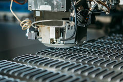 Close up of cnc punching press machine with metal plate. Industry Stock Images