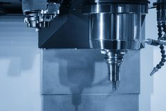 Close up of the CNC spindle. With the cutting tool and holder in the light blue scene.The CNC machining center for hi-technology manufacturing Royalty Free Stock Images