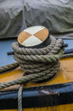 Close up of coarse rope tied around a coloured wooden bollard. Stock Image