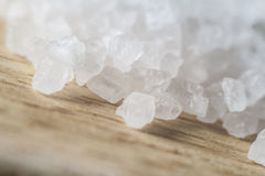 Close-up of coarse sea salt. Macro close-up  of coarse sea salt spilled on wooden board Royalty Free Stock Photos