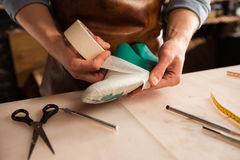 Close up of a cobbler modeling mens shoe. At his workshop Stock Photo