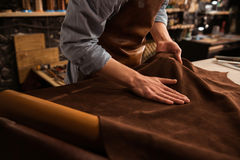Close up of a cobbler working with leather textile. Close up of a male shoemaker working with leather textile at his workshop stock images