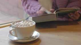 Close up of cocoa cup. Cocoa with marshmallows and woman reading book stock video