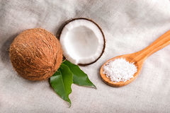 Close-up coconuts on a gray fabric background. Bright cut coco, two green leaves and spoon filled with white coconut chips. Stock Photo