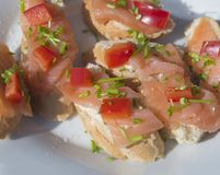 Close up coctail snack, bread with smoked salmon, pepper and cho. Pped chive on white plate, selective focus Royalty Free Stock Photo
