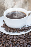 Close up of coffe cup and saucer surrounded by beans on hessian Stock Photos