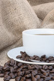 Close up of coffe cup and saucer surrounded by beans on hessian Royalty Free Stock Image