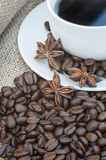 Close up of coffe cup and saucer surrounded by beans on hessian Stock Photo