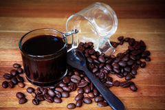 Close up of coffee bean and shot of black coffee on wood table Royalty Free Stock Image
