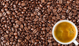 Close-up of coffee beans background and white coffee cup Royalty Free Stock Photos