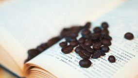 Close up coffee beans and and book on wooden table royalty free stock image