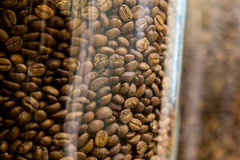 Close up of coffee beans in clear glass jars. Selective focus with shallow depth of field Royalty Free Stock Images