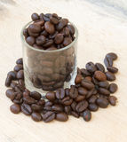 Close up of coffee beans and a cup full of coffee.  Royalty Free Stock Image