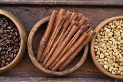 Close up of coffee beans in wooden bowl and cinnamon Royalty Free Stock Photography