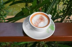 Close up coffee cappuccino on wooden balcony.  Stock Photography