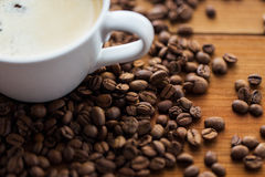 Close up coffee cup and beans on wooden table Royalty Free Stock Photo