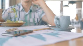 Close up of coffee cup being put on cafe tabe in front of businessman. Concept of: coffee drinking, graphs and charts, business people, cafe table stock video footage