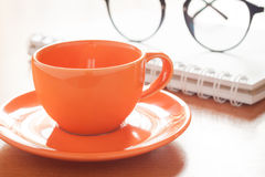 Close up of coffee cup with book and eyeglasses Stock Photography