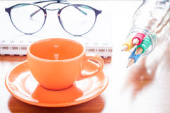 Close up of coffee cup with book and eyeglasses Stock Images