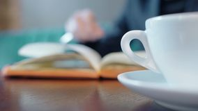 Close up of coffee cup on the cafe table with person turning over the pages of book at the background. stock footage