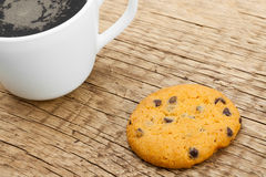 Close up of coffee cup and a cookie on old rustic wooden table Royalty Free Stock Image