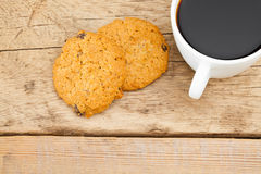 Close up of coffee cup and a cookie on wooden table Stock Photo