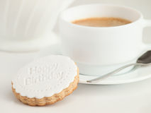 Close up of coffee cup and fondant covered cookie. Happy birthday decoration on top. Stock Photos
