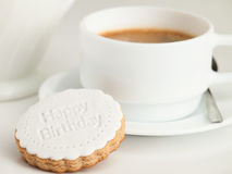 Close up of coffee cup and fondant covered cookie. Happy birthday decoration on top. Stock Photography