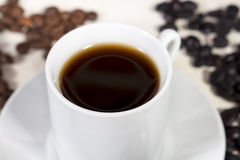 Close-up of coffee cup in front of different coffee beans Royalty Free Stock Images